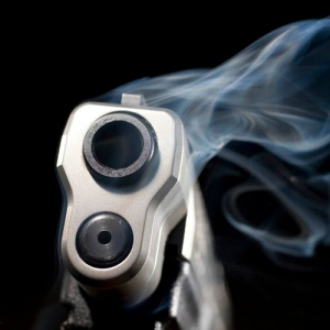 Blue smoke that is rising from the muzzle of a handgun